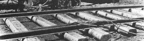 Tie choppers hand-hewed two flat faces on felled logs using a broad axe, then stripped the bark off the remaining sides. The finished tie was suitable for laying track.