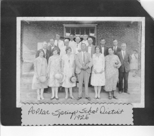 "1926 Poplar Springs Consolidated School opening. Inscription on building reads ""Poplar Springs School District, Minerva Academy. Trustees: A. J. Guthrie, Chairman, J. L. Hughes, Secretary and Treasurer, N. L. Singletary; Originators of Consolidation, Moses G. Sirmons, S. M. Green, Dr. J. R. Lasseter; William G. Avera, Designer of Building, W. E. Register, Builder 1926."" Teachers, Annie Lee Nix Maddox, Golie Spells, _____Sike, Charlie E. Parham, Alice Knight. (It is thought that many of the above-named persons are in this photo; Wm (Bill) G. Avera, School Superintendent, is the man with left hand against his chest, near middle of 2nd row.) Image courtesy of berriencountyga.com"