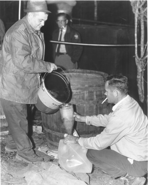 Destruction of a Berrien County moonshine still, 1960. On the left is Georgia Department of Revenue agent Kay Devane. The man kneeling on the right may be Revenue Agent J. H.Touchton of Ray City, GA. (Image courtesy of www.berriencountyga.com)