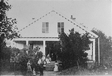 Home of Judge Augustin H. Hansell circa 1884, Thomasville, GA. On porch, Mrs. Hansel and Judge Hansell; sitting on top step, Miss Sallie Hansell; on bottom step, Jim Jarrett; at foot of steps, Nannie Boles; standing in yard, left to right, Mrs. James Watt, William A Watt, Hansel Watt, Mr. James Watt.