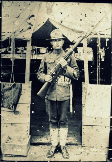 "Josea Peeples ""Hod"" Clements, 1918, , dressed in his World War I uniform and holding his rifle."