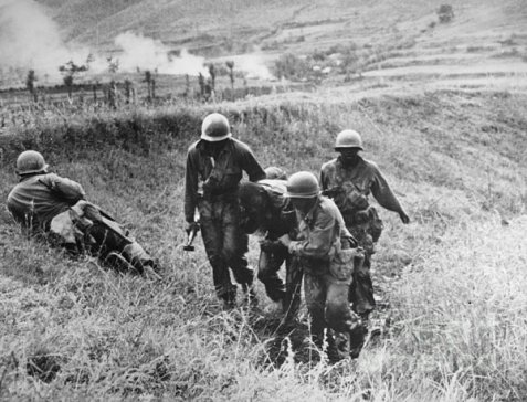 U. S. Infantrymen helping a wounded soldier.  Image Source: National Archives