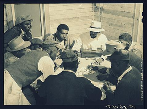 "Title: Migratory laborers and vegetable pickers playing ""skin"" game in back of juke joint and bar in the Belle Glade area of south central Florida. Image source: Library of Congress, http://www.loc.gov/pictures/item/fsa2000037636/PP/"