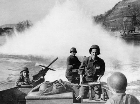 March, 1945, A U.S. Navy landing craft with dropping depth charges on the Rhine River to detonate possible mines and discourage saboteur attacks on pontoon bridges.  Naval personnel involved in the Rhine crossings were required to wear Army uniforms.