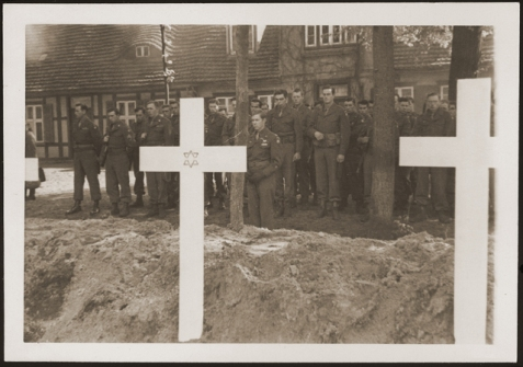 After the liberation of the Wöbbelin concentration camp, the US Army ordered the local townspeople to bury the corpses of prisoners killed in the camp. This photograph shows troops observing a moment of silence at a mass funeral for victims of the Wöbbelin camp. Germany, May 7, 1945. J. I. Clements, Jr. , of Ray City, GA was among the soldiers present on that day.