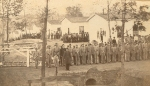 Rock Island Prison, Rock Island, IL. Federal guards stand in the foreground; in the background confederate POWs turn out for roll call, December 3, 1863.