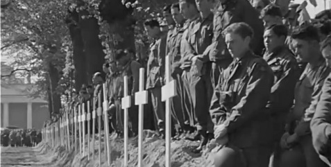 Soldiers view burials of victims from Wobbelin Concentration Camp at Ludwiglust, Germany. May 7, 1945.