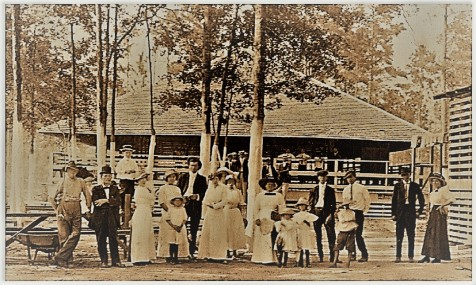 Posing in front of the roller skating rink at Mayhaw Lake in 1914, left to right: Burton Moore; Tom Parrish; Manson Johnson; unidentified lady; Charlie Ruth Shaw with her husband, Bruner Shaw, and daughter, Juanita Shaw; lady; Viola Smith Davis; lady; Mrs. Burton Moore and daughters, Kate Hazen, Thelma Register; Lonnie Smith; boy; man; Shellie Ziegler; and Jessie Ziegler Touchton. Members of the band in the background include: Rossie Swindle, Glenn Johnson, Lonnie Swindle, and J. H. Swindle.