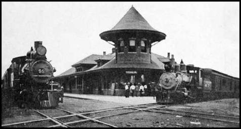 Vidalia's Union Station, built in 1912-13 at the junction of the tracks of the Georgia & Florida Railroad (right) and Seaboard Air Line Railway (left). Located at the far western edge of Railroad Avenue, facing the bisected block of Leader and Main streets, the brick passenger depot (Union Station) was a fish hook-shaped building dominated by its two-story corner tower with bellcast conical roof. It also featured a Ludowici tile roof, dormer windows, and wide overhanging eaves with brackets. The water tower, which was the tallest structure in the area for nearly forty years, stood almost directly in front of Union Station. The tank's swivelling hoses pivoted almost 360 degrees, enabling trains to be serviced from either side of the structure. East of Union Station along Railroad Avenue was the first freight depot. Image source: https://railga.com/Depots/vidalia.html