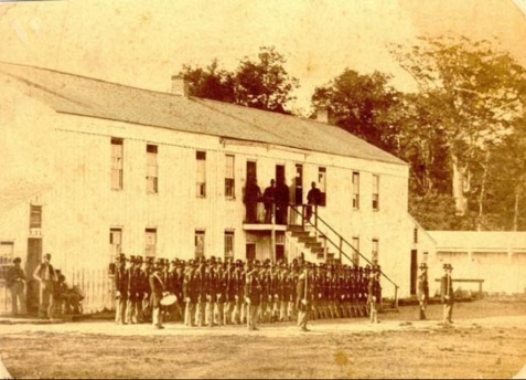 Company of Johnson's Island Prison guards at roll call. The barracks building was the same type built for the prisoners. The lean-to buildings on each end were kitchens. In the background is a portion of the stockade wall showing the parapet used by the guards while on duty. http://johnsonsisland.org/history-pows/civil-war-era/